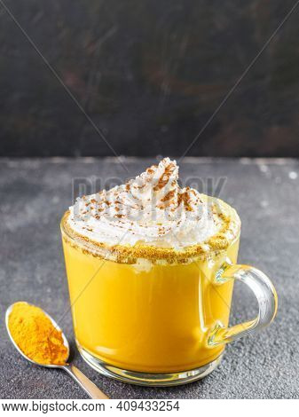 Healthy Drink Golden Turmeric Latte With Whipped Cream In Glass Cup. Gold Milk, And Dried Turmeric P