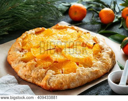 Close Up View Of Caraway And Orange Tart On Baking Paper Over Black Cement Background. Winter Season