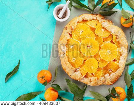 Top View Of Caraway And Orange Tart On Baking Paper Over Blue Concrete Background With Copy Space.wi