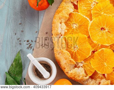 Top View Of Caraway And Orange Tart On Baking Paper Over Gray Wooden Table With Copy Space.winter Se
