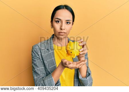 Young hispanic girl holding piggy bank relaxed with serious expression on face. simple and natural looking at the camera.