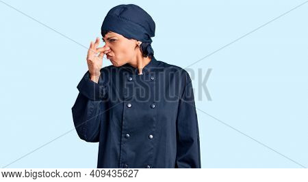 Young brunette woman with short hair wearing professional cook uniform smelling something stinky and disgusting, intolerable smell, holding breath with fingers on nose. bad smell