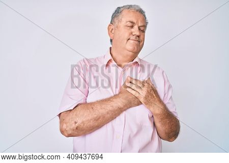 Senior grey-haired man wearing casual clothes smiling with hands on chest, eyes closed with grateful gesture on face. health concept.