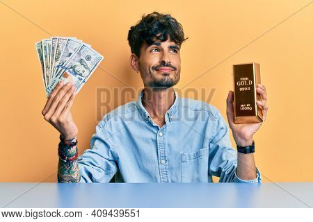 Young hispanic man holding dollars and gold ingot smiling looking to the side and staring away thinking.