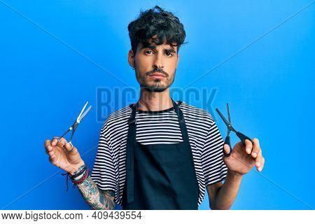 Young hispanic man wearing barber apron holding scissors relaxed with serious expression on face. simple and natural looking at the camera.