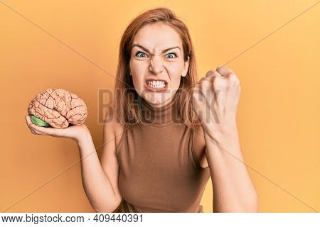 Young caucasian woman holding brain annoyed and frustrated shouting with anger, yelling crazy with anger and hand raised