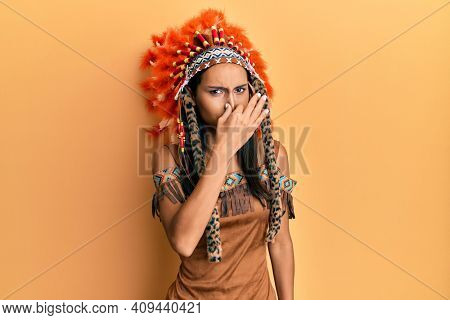 Young brunette woman wearing indian costume smelling something stinky and disgusting, intolerable smell, holding breath with fingers on nose. bad smell