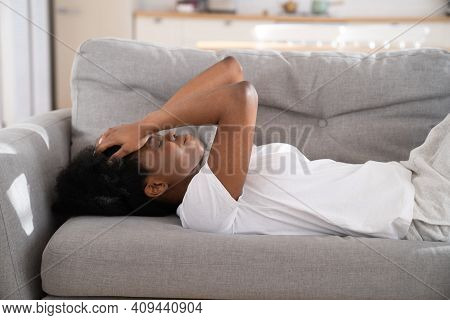 Sad Depressed Young African Woman Lying On Couch At Home Crying, Feeling Loneliness, Suffering From