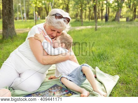 Woman With Kid Spending Time Together Outdoors. Happy Grandma With Grandson Embracing. Senior Granny