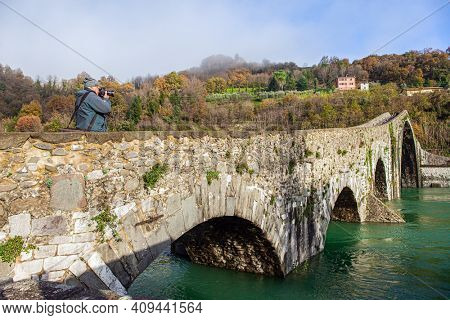 Elderly tourist photographs a magnificent landscape. Ponte della Maddalena Bridge. Cold green waters of the Sercchio River. Italy. Province of Tuscany. Cold windy winter day
