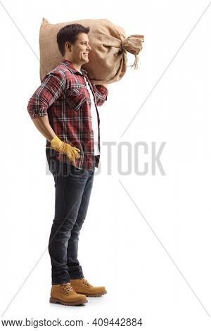 Full length profile shot of a young farmer carrying a sack on his shoulder isolated on white background