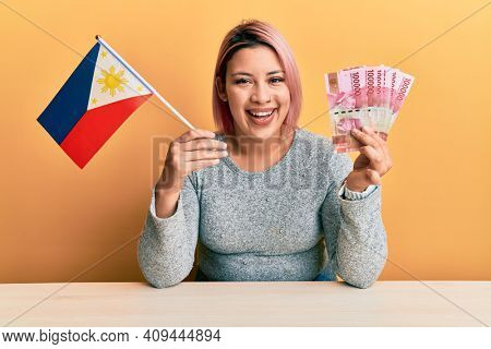 Hispanic woman with pink hair holding philippine flag and philippines pesos banknotes smiling and laughing hard out loud because funny crazy joke.