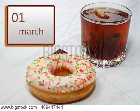 March 1 ,1st Day Of The Month. Calendar With Date And A Cupcake With Glass Of Tea On Table At Home..