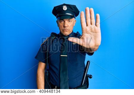Handsome middle age mature man wearing police uniform doing stop sing with palm of the hand. warning expression with negative and serious gesture on the face.