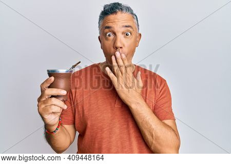 Handsome middle age mature man drinking mate infusion covering mouth with hand, shocked and afraid for mistake. surprised expression