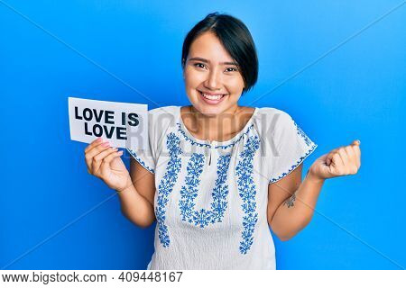 Beautiful young woman with short hair holding paper with love is love message screaming proud, celebrating victory and success very excited with raised arm