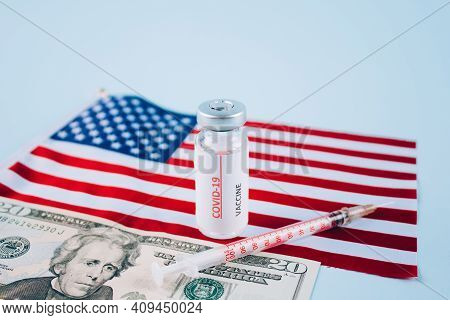 Covid-19 Vaccine Vials With 20 Dollars Bill Against Usa Flag On Blue Background With Copy Space For