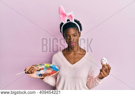 Young african american girl wearing cute easter bunny ears painting egg relaxed with serious expression on face. simple and natural looking at the camera.