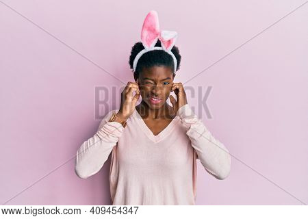 Young african american girl wearing cute easter bunny ears covering ears with fingers with annoyed expression for the noise of loud music. deaf concept.