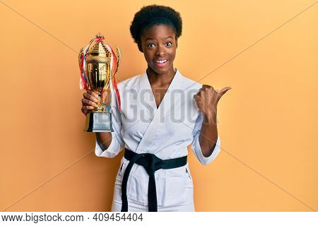 Young african american girl wearing karate kimono holding trophy pointing thumb up to the side smiling happy with open mouth