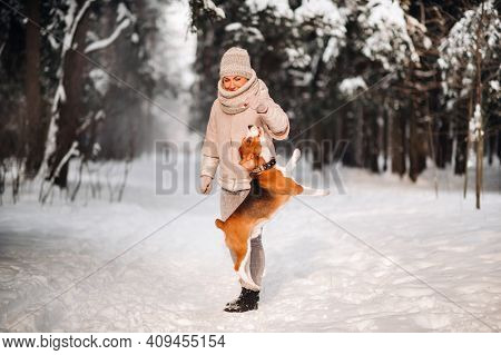 A Woman On A Winter Day With Her Pet Dog Beagle In The Winter Forest Playing