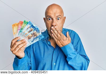 Middle age bald man holding swiss franc banknotes covering mouth with hand, shocked and afraid for mistake. surprised expression