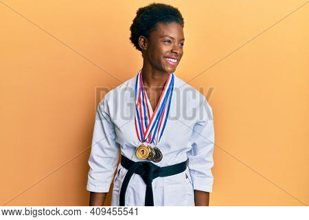 Young african american girl wearing karate kimono and black belt looking away to side with smile on face, natural expression. laughing confident.