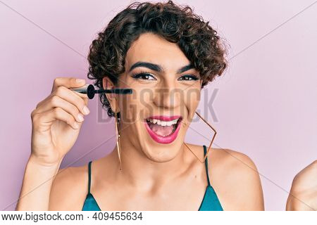 Young man wearing woman make up holding eyelash mascara celebrating achievement with happy smile and winner expression with raised hand