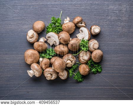Brown colored edible mushrooms or cremini mushrooms on black table with herbs. Top view.
