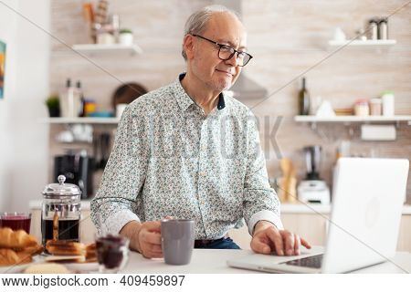 Mature Man Typing On Laptop In Kitchen During Breakfast And Driking Coffee. Elderly Retired Person W