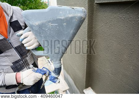 A Building Contractor Is Renovating, Rendering Exterior Walls Of The House, Applying Stucco, Spaying