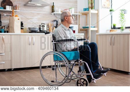 Lonely Invalid Man Sitting In Wheelchair Looking Through Kitchen Window. Elderly Handicapped Pension
