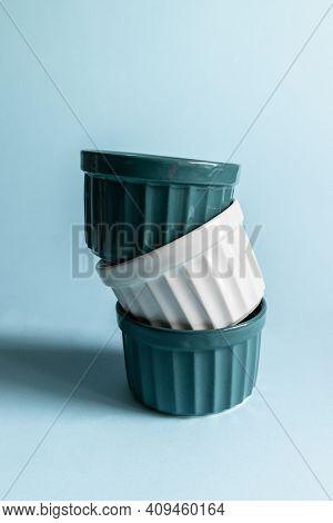 Ceramic Round Ramekins On A Blue Background. Vertical Photo