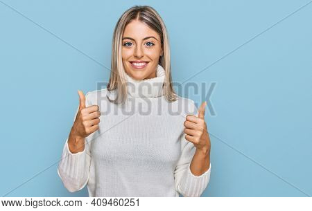 Beautiful blonde woman wearing casual turtleneck sweater success sign doing positive gesture with hand, thumbs up smiling and happy. cheerful expression and winner gesture.