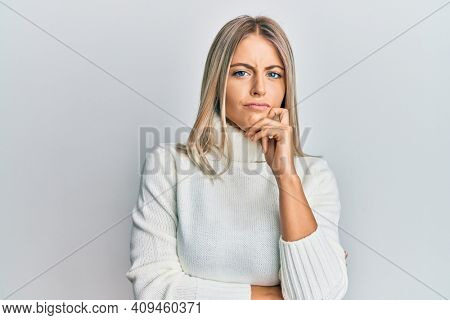 Beautiful blonde woman wearing casual turtleneck sweater thinking concentrated about doubt with finger on chin and looking up wondering