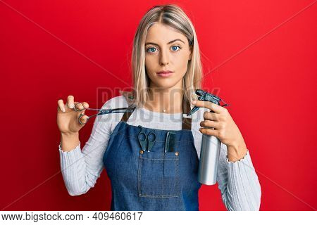 Beautiful blonde woman wearing hairdresser apron and holding scissors relaxed with serious expression on face. simple and natural looking at the camera.
