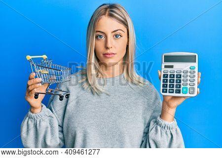 Beautiful blonde woman holding small supermarket shopping cart and calculator relaxed with serious expression on face. simple and natural looking at the camera.