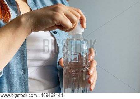 Woman Hand Opening Water Bottle On A Gray Background. Drinking Mineral Water From Bottle