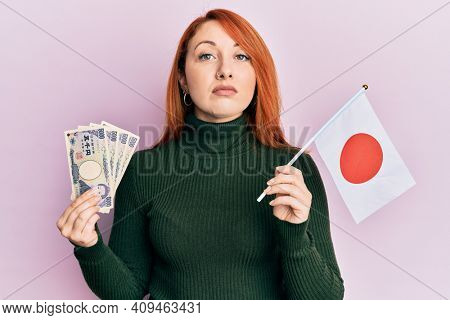 Beautiful redhead woman holding 5000 japanese yen banknotes and japan flag relaxed with serious expression on face. simple and natural looking at the camera.