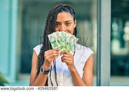 Young african american woman covering mouth with norwegian 50 krona banknotes at the city.