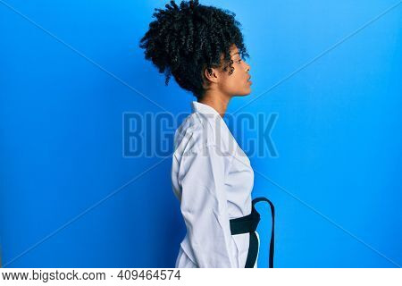 African american woman with afro hair wearing karate kimono and black belt looking to side, relax profile pose with natural face with confident smile.