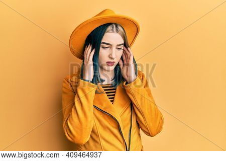Young modern girl wearing yellow hat and leather jacket covering ears with fingers with annoyed expression for the noise of loud music. deaf concept.
