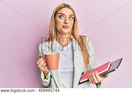 Young caucasian woman drinking a cup of coffee and holding laptop smiling looking to the side and staring away thinking.