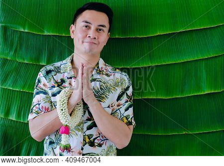 Thai Man Doing Pay Respect Posture With Jasmine Garland On His Arm To Do Blessing For Songkran Festi
