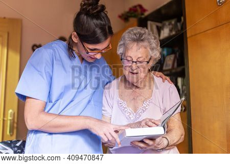Happy Senior Woman With Her Caregiver At Home Reading A Book. Senior Home Care Concept.