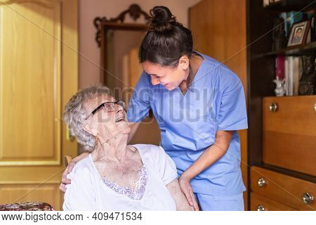 Happy Senior Woman Laughing  With Her Caregiver At Home. Senior Home Care Concept.