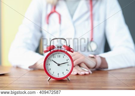 Red Alarm Clock On Background Of Doctor In White Coat. Medical Insurance Concept