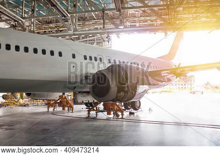 White Passenger Airliner Under Maintenance In The Hangar. Repair Of Jet Plane Engine On The Wing And