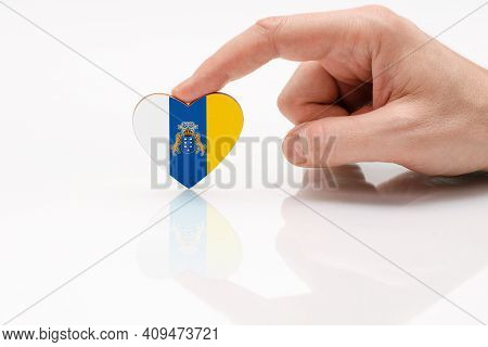 Flag Of The Canary Islands. Love And Respect Canary Islands. A Man's Hand Holds A Heart In The Shape