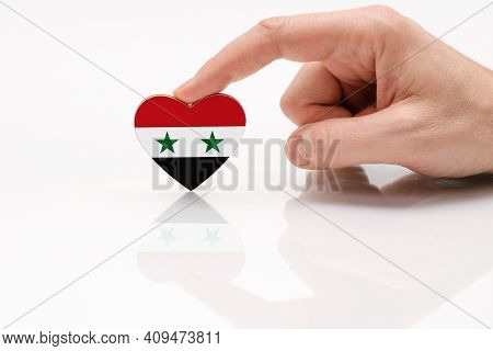 Syria Flag. Love And Respect Syria. A Man's Hand Holds A Heart In The Shape Of The Syria Flag On A W